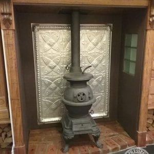 pressed tin panels carousel frame feature behind pot belly stove